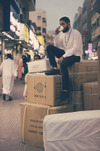 A man sitting on cardboard boxes in a street