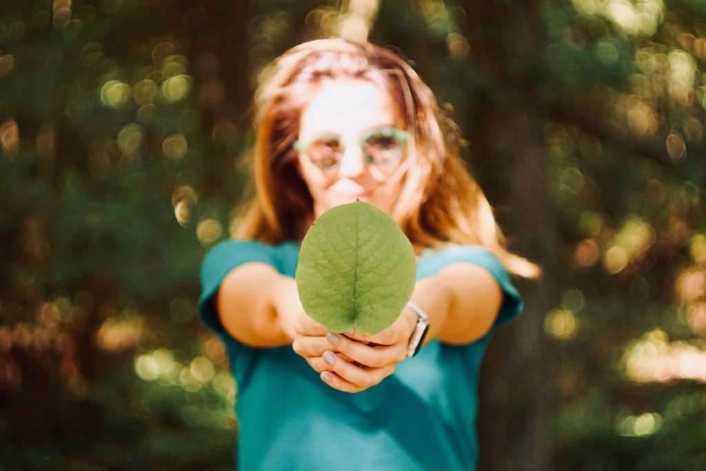 Girl holding a leaf to signify the importance of green moving supplies