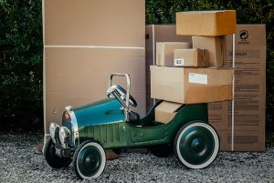 A green small vehicle next to stacked cardboard boxes.