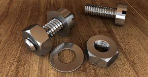 Several different screws and bolts on a wooden background