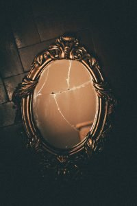 A brass mirror, laying broken on the floor over a simple packing mistake