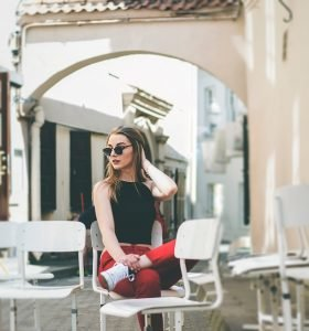 A girl wearing sunglasses sitting on a white chair.