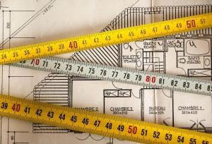Measuring tape over a blueprint of a home.