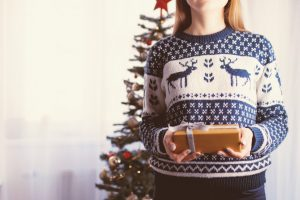 Woman holding a present in a Christmas sweater in front of a decorated tree