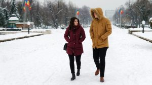 A man and woman walking in the snow in winter jackets