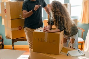 A woman leaning on a moving boxes labeled as fragile.