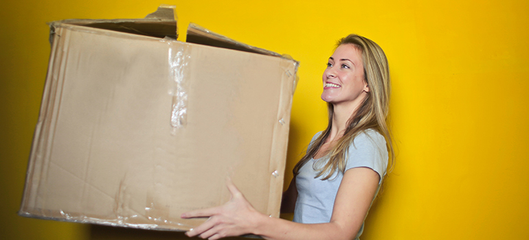 Woman holding a used cardboard box representing used moving supplies.