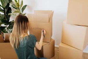 A woman labeling boxes for a move.