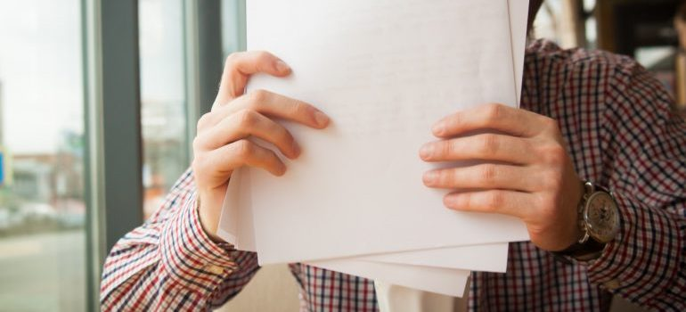 A person holding paperwork.