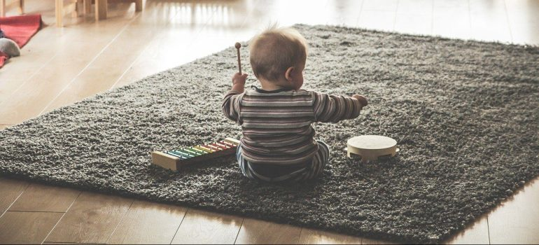 A child sitting on a carpet playing with new toys after getting rid of old and broken toys.
