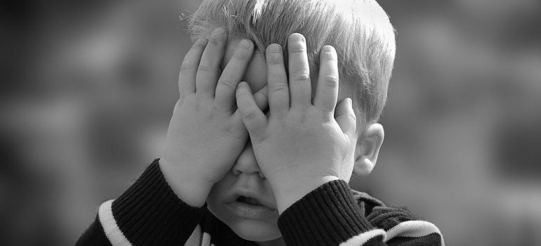 a child covering his face with his hands