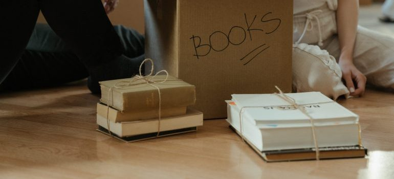 A labeled moving box containing books.