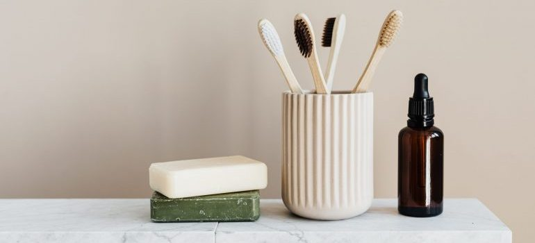 Toothbrushes in a ceramic jar and other toiletries.