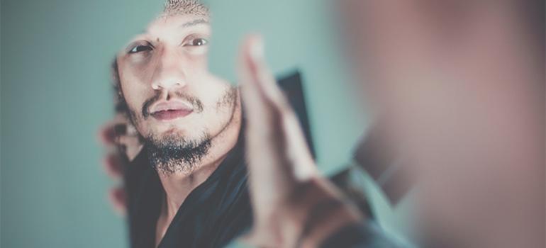 A man holding apiece of a broken mirror.