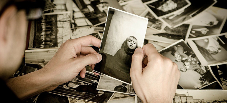 A man holding a photo, thinking about packing your old photos for relocation