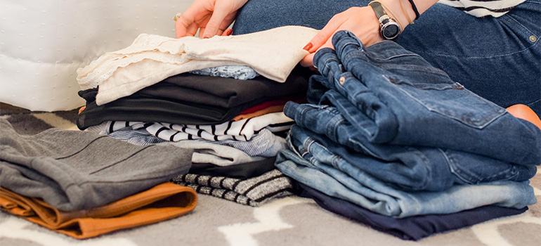 A woman sorthing clothes into piles