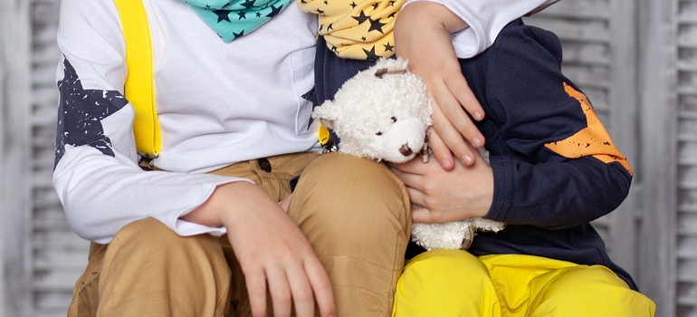 Two kids hugging and holding a teddy bear.