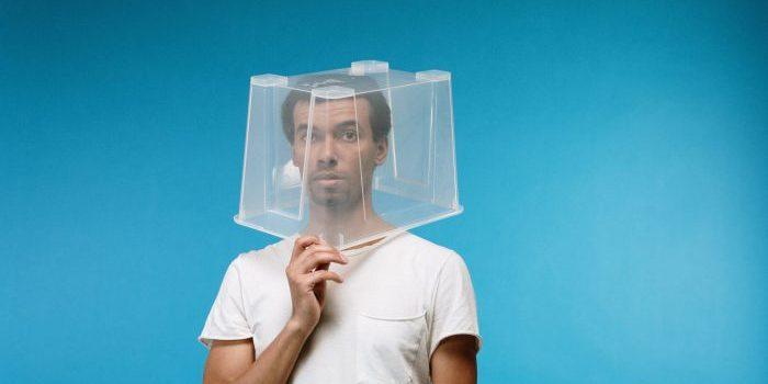 Man with plastic bin on his head.