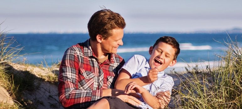 A father and a son laughing on the beach