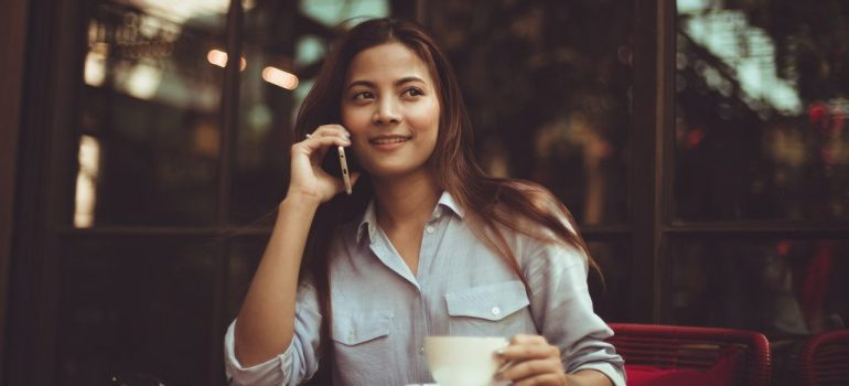 a woman negotiate with NYC movers on the phone while drinking coffee