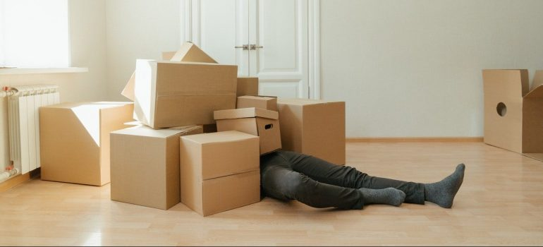 a man under a large quantity of cardboard boxes