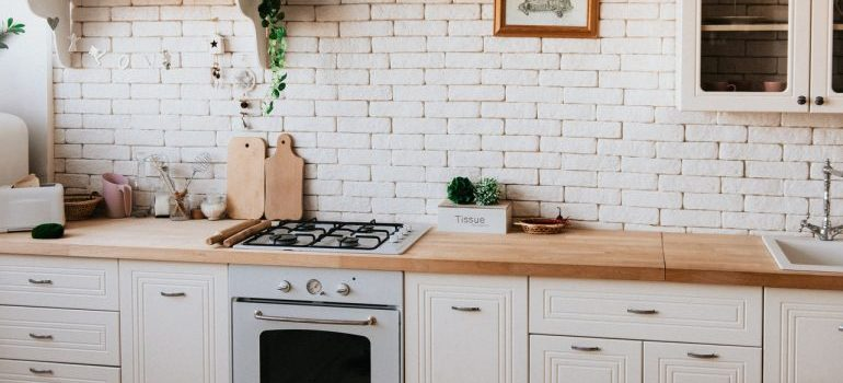 A clean white kitchen with tiles.