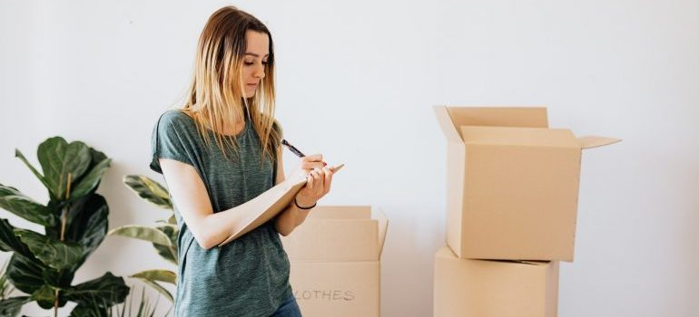 Woman writing down notes during while packing