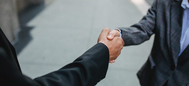 two men in black suits shaking hands on the street
