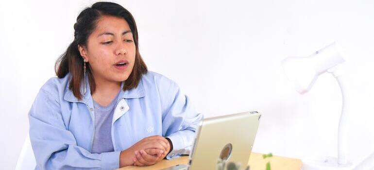 A woman looking at her lap top trying to find the right moving boxes