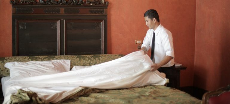 A man who is giving a good example on how to pack your linens for relocation.