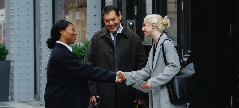 Two women shaking hands while a man watches.