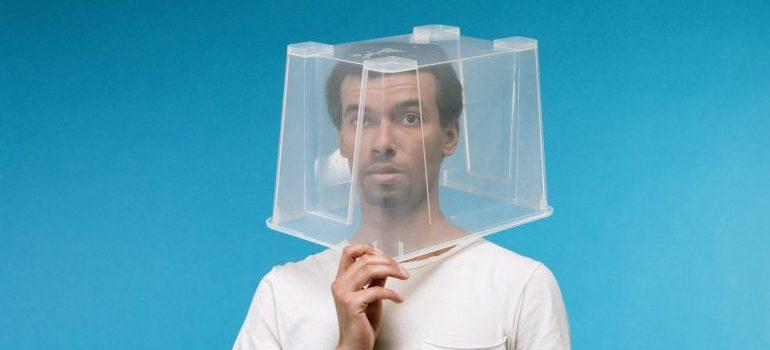 man having plastic box on the head