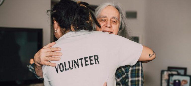 volunteer bringing supplies to elderly male person, hugging
