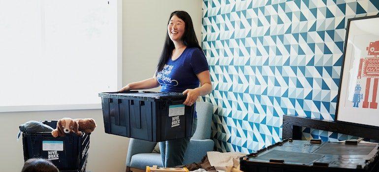 woman holding moving bin