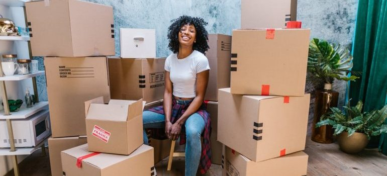 woman smiling and sitting in between moving boxes