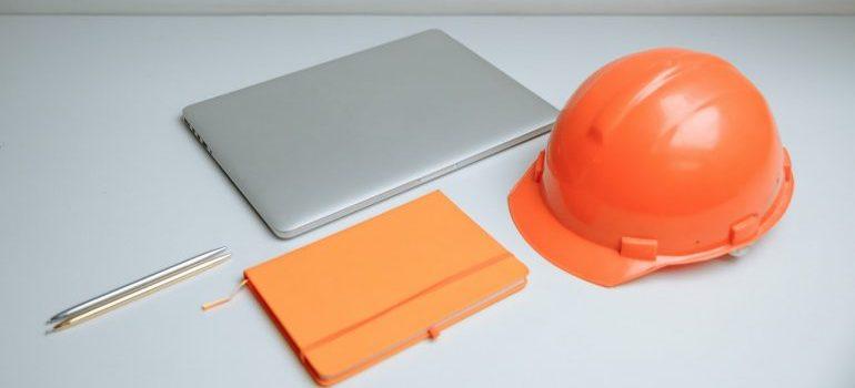 Silver Macbook beside orange safety helmat