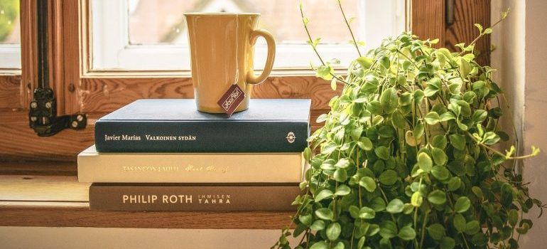 Three books and a cup on top of them.