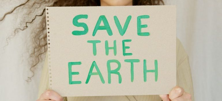 The girl holding a sign that says save the earth