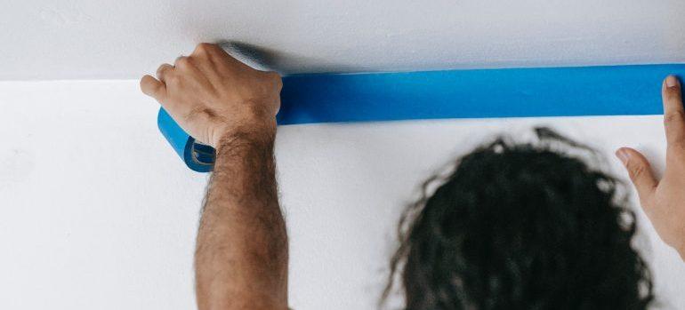 man putting masking tape