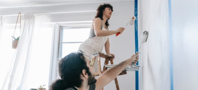 two people painting walls