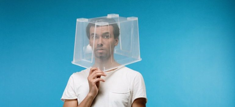 man with plastic moving box on his head