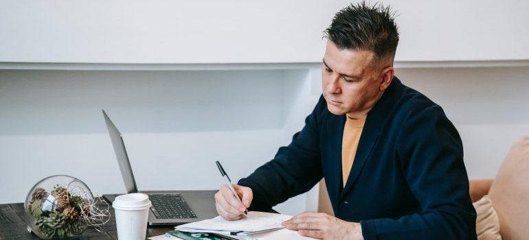 Man writing down online moving reviews