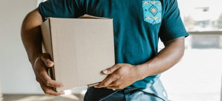 Man holding a box prepared for packing your shed