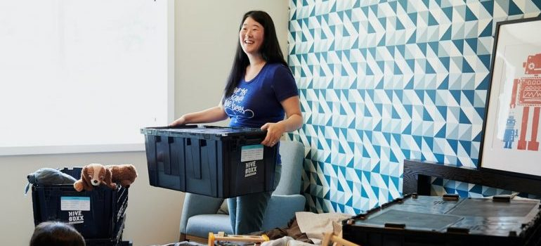 A woman smiling because proper moving supplies protect your possessions
