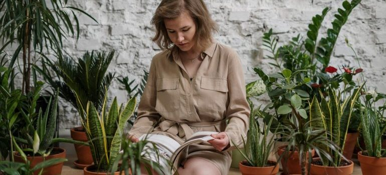 Girl sitting in on the floor surrounded with plants and reading.