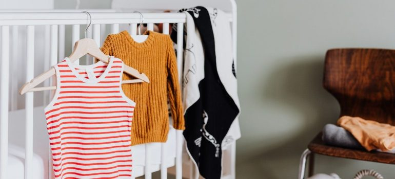 a part of the process where you should store outgrown baby clothes by separating them into groups