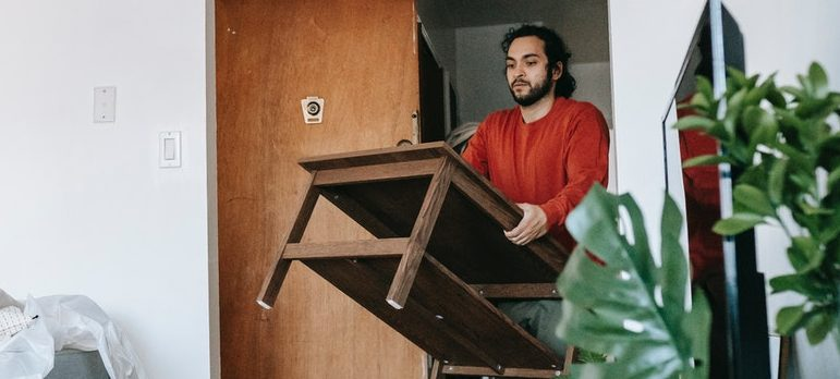 Man moving table ready to donate your old furniture