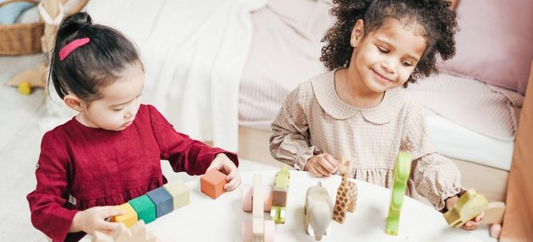 Two little girls playing with toys.