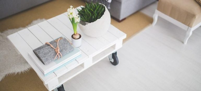 White coffee table with flowers and book