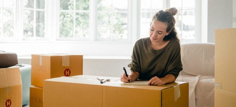 a woman writing a label on the box as she is moving out after divorce